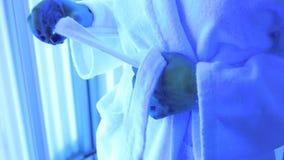 Het close-up van een meisje laat een riem op een Badjas los die zich in een Solarium bevinden stock videobeelden