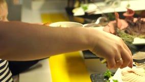 Het close-up van een meisje met tang neemt een gesneden worst Het buffet van de catering stock video