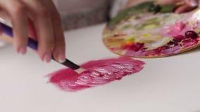 Het close-up van een meisje in a trekt op een witte canvas roze verf met een borstel stock footage