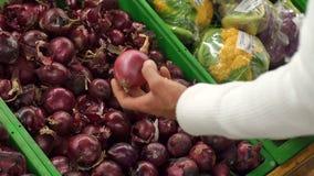 Het close-up van een mens kiest rode uien in een supermarkt Langzame Motie stock footage