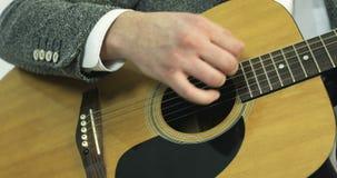 Het close-up van een mensen` s hand raakt de koorden op een akoestische gitaar stock footage