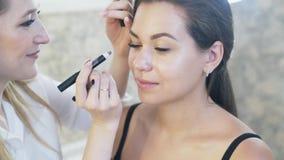 Het close-up van een stilist, grimeur maakt oogmake-up van een model Een beroeps maakt Smokey bij hulp van een vet potlood stock video