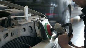 Het close-up van een werktuigkundige poetst de koplamp met een malende machine op stock video