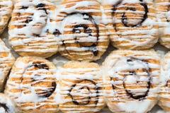Het close-up van eigengemaakte veganistkaneel rolt in pan en gemotregend met vanille het berijpen royalty-vrije stock foto's