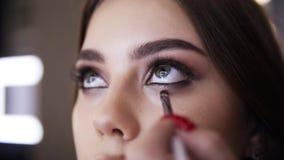 Het close-up van grimeurhand met het klein borstelwerk door het lagere ooglid, maakt rokerige oogmake-up Mooi stock footage