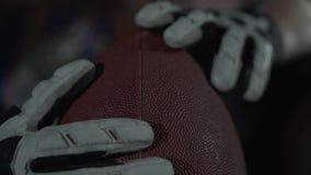 Het close-up van handen van een beroeps stemde atleet die sportenhandschoenen draagt houdend een rugbybal stock footage