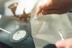 Het close-up van handen van professionele windschermhersteller vult een barst in het glas met een speciaal polymeer door a royalty-vrije stock foto's