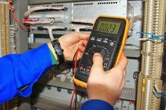 Het close-up van ingenieurs` s handen met een industrieel kabinet van de multimetertest relaisbescherming en automatisering Stock Foto