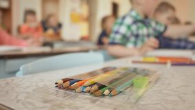Het close-up van kleurenpotloden op de lijst in de kinderen` s kleuterschool Het schilderen stock videobeelden