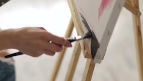 Het close-up van kunstenaarsmeisje trekt zwarte verf in de hoek van het canvas stock videobeelden