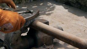 Het close-up van man dient het werkhandschoenen in, die de oude pijp van roest met een metaalborstel schoonmaken stock videobeelden