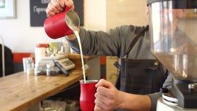 Het close-up van mannelijke Barista giet melk in een Kop, het proces om een latte voor te bereiden stock video
