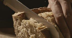 Het close-up van mensen` s handen sneed vers zacht brood op een houten raad stock video
