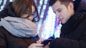 Het close-up van Mooi paar gebruikt mobiele toepassing in de sneeuwavond, Kerstmis en het Nieuwjaar stock video