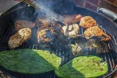 Het close-up van nopalescactus en banaanblad verpakte vissen en kip en varkensvlees op een houtskoolgrill met rook en een binnen  stock foto