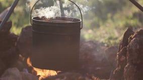 Het close-up van pot met voedsel hangt over de brand stock videobeelden