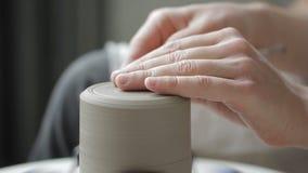Het close-up van pottenbakkers` s hand maakt een groef op de bodem van een kleimok stock videobeelden
