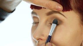 Het close-up van professionele grimeur die dagelijkse make-up doen, zet poeder op de wangen van de vrouw met borstel stock videobeelden