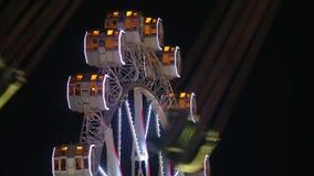 Het close-up van Reuzenrad en unfocused carrousel door te roteren bij nacht stock video