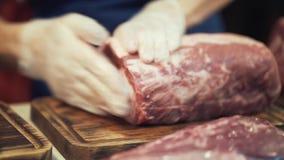 Het close-up van slager dient witte beschermende handschoenen in voorbereidend een grote besnoeiing van vlees voor het koken of v stock footage