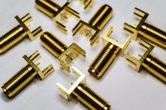Het close-up van verspreid goud plateerde componenten van de de schakelaarselektronika van SMA de mannelijke op witte achtergrond stock foto