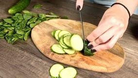 Het close-up van vrouwelijke handen die komkommers op een wandelwagen op een knipselraad snijden naast gehakte munt gaat weg Gezo stock footage