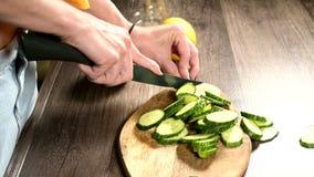 Het close-up van vrouwelijke handen die komkommers op een wandelwagen op een knipselraad snijden naast gehakte munt gaat weg Gezo stock video