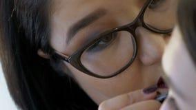 Het close-up van vrouwelijke kunstenaar trekt een lijn op gezicht van het model stock videobeelden