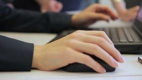 Het close-up van wijfje dient het kostuumwerk met muis over laptop in stock footage