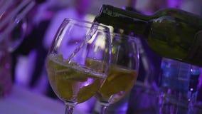 Het close-up van wijnglas giet witte wijn in nachtclub Kader Gietende alcoholische dranken in glazen voor nachtpartij stock videobeelden