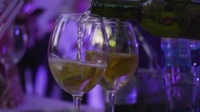 Het close-up van wijnglas giet witte wijn in nachtclub Kader Gietende alcoholische dranken in glazen voor nachtpartij stock video