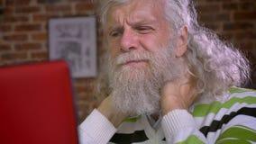 Het close-up vermoeide zeer gezicht van de hogere Kaukasische mens met witte lange baard en het haar masseert zijn hals en bekijk stock footage