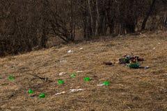 Het close-up verspreidde huisvuil en partijen plastic koppen op de lentegras verlaten door toeristen in bergen in bos stock afbeeldingen