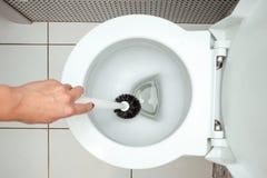 Het close-up, Vrouwelijke hand wast een toiletborstel Het concept netheid in het huis, hygiëne, toilet, microben royalty-vrije stock foto