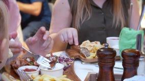 Het close-up, vrouwelijke handen die vorken gebruiken neemt snel voedsel van een houten schotel 4K stock footage
