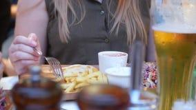 Het close-up, vrouwelijke handen die vorken gebruiken neemt snel voedsel van een houten schotel 4K stock video
