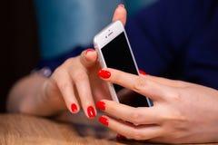 Het close-up, vrouwelijke handen met rode manicure gebruikt een smartphone op een witte achtergrond beperkte diepte van gebied royalty-vrije stock foto's