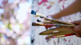 Het close-up, vrouwelijke handen, schilder, kunstenaar schildert een beeld van bloemen in de bloeiende boomgaard van de de lentea stock videobeelden