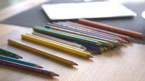 Het is close-upbeeld van vrouw die kleurrijke potloden op lijst zetten stock footage