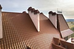 Het close-updetail van de bouw van steile dakspaandak en baksteen pleisterde schoorstenen op huisbovenkant met het dak van de met royalty-vrije stock afbeelding