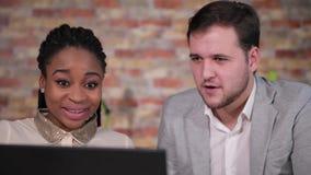 Het close-upgezicht van gelukkige bedrijfsmensen kijkt aan laptop in het bureau stock video