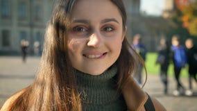 Het close-upgezicht van gorgeoud Kaukasisch meisje met lange donkere erfgenaam en bruine ogen bekijkt camera calmly met glimlach  stock footage