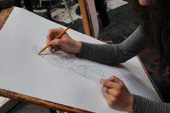 Het close-uphanden van de kunststudent bij bureautekening met potlood stock afbeelding