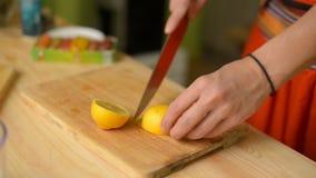 Het close-upmeisje snijdt een citroen op een houten scherpe raad stock footage