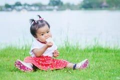 Het close-upmeisje zit op grasvloer etend cracker op de parkachtergrond royalty-vrije stock foto