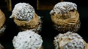 Het close-uppanorama neer op rijen van Frans desserts choux gebakje vulde met karamelroom stock video