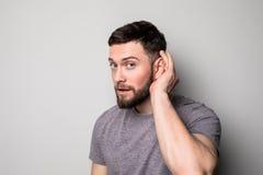 Het close-upportret mens het plaatsen overhandigt op oor luisteren zorgvuldig geïsoleerd op grijze muurachtergrond stock afbeelding