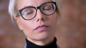 Het close-upportret van B-kortere wegvrouw in glazen die haar aanpassen en calmly op in camera letten bricken muur stock videobeelden