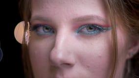 Het close-upportret van blond model draait aan camera en let ernstig langzaam op het knipperen op vage lichten stock videobeelden