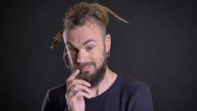 Het close-upportret van de freaky mens met dreadlocks en het doordringen zorgvuldig wat betreft zijn baard krijgt inzicht op zwar stock videobeelden